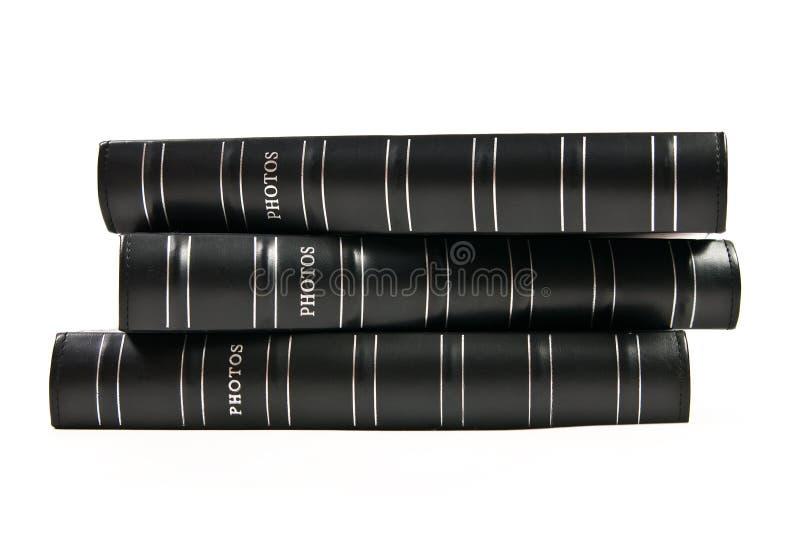Pila de tres álbumes de foto negros aislados imagen de archivo libre de regalías