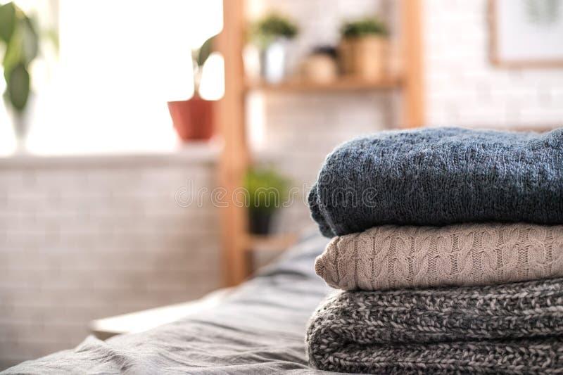 Pila de tres suéteres hechos punto en cama imagenes de archivo