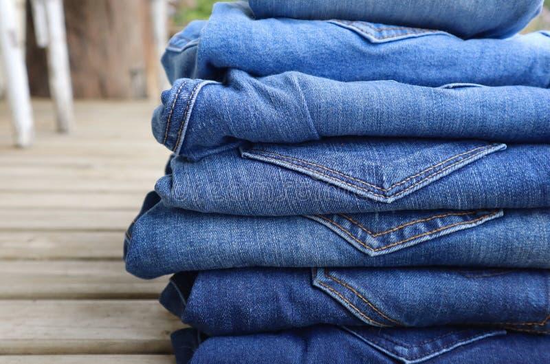 Pila de vaqueros azules doblados del dril de algodón en una variedad de sombras imagen de archivo libre de regalías