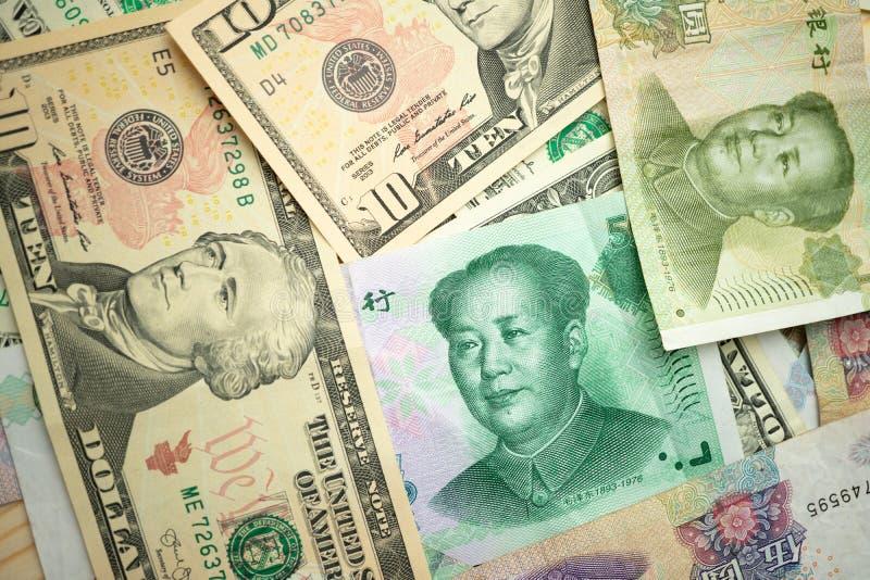 Pila del dólar americano y billetes de banco chinos del yuan en la tabla el concepto de una guerra comercial entre los Estados Un foto de archivo