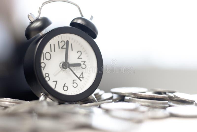 pila del despertador y de la moneda en la tabla Inversión del tiempo y tiempo del paso foco seleccionado y suave en el reloj imágenes de archivo libres de regalías