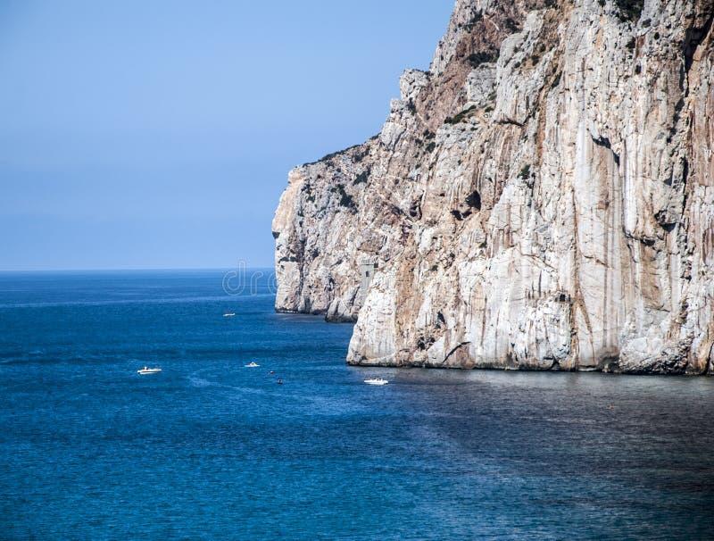 Pila del mar de Masua diaria y algunos barcos en el verano (Cerdeña-Yo foto de archivo