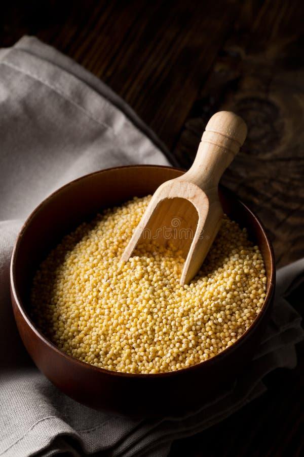 Pila del mijo de oro, una semilla libre del grano del gluten, en cuenco de madera en la toalla de cocina gris en la tabla de coci fotos de archivo libres de regalías