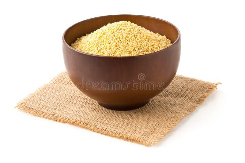 Pila del mijo de oro, una semilla libre del grano del gluten, en cuenco de madera en tela de la arpillera sobre blanco fotografía de archivo
