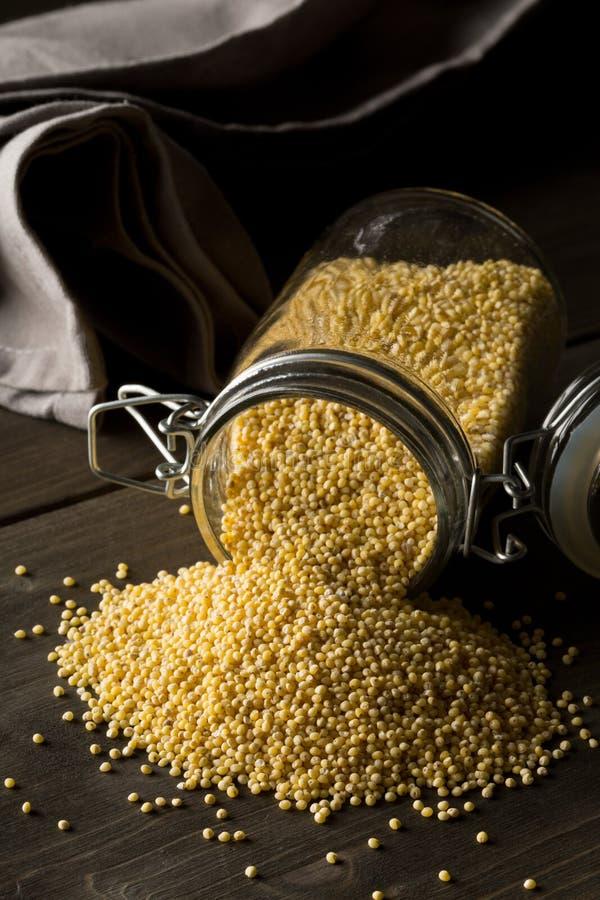 Pila del mijo de oro, una semilla libre del grano del gluten, en el tarro de cristal del almacenamiento en fondo oscuro de la tab foto de archivo
