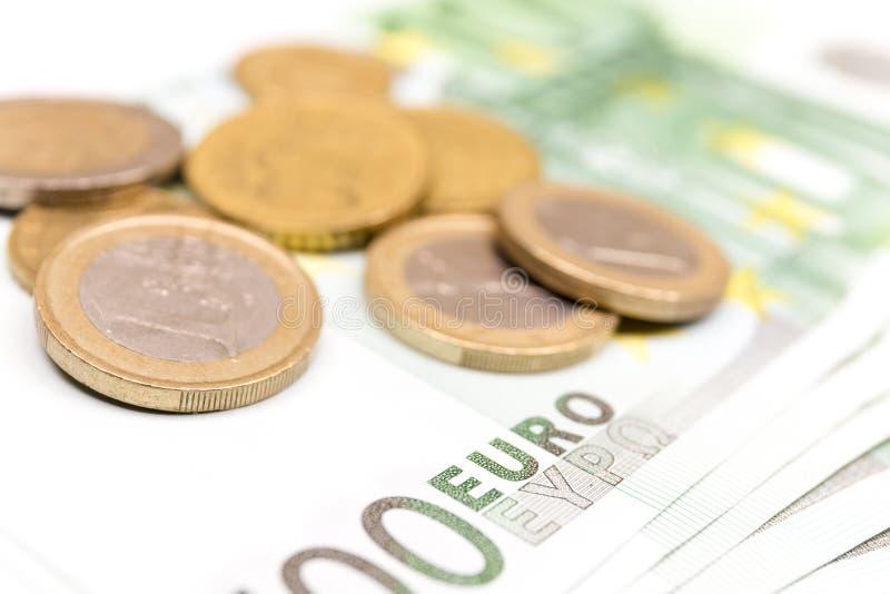 Pila del primo piano di euro banconote e monete 100 euro banconote immagini stock libere da diritti