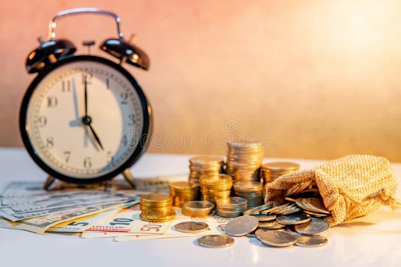 Pila del reloj y de la moneda en la tabla Inversión del tiempo fotos de archivo libres de regalías