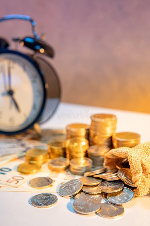 Pila del reloj y de la moneda en la tabla Inversión del tiempo foto de archivo libre de regalías