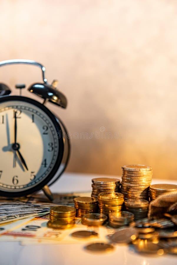 Pila del reloj y de la moneda en la tabla Inversi?n del tiempo imágenes de archivo libres de regalías