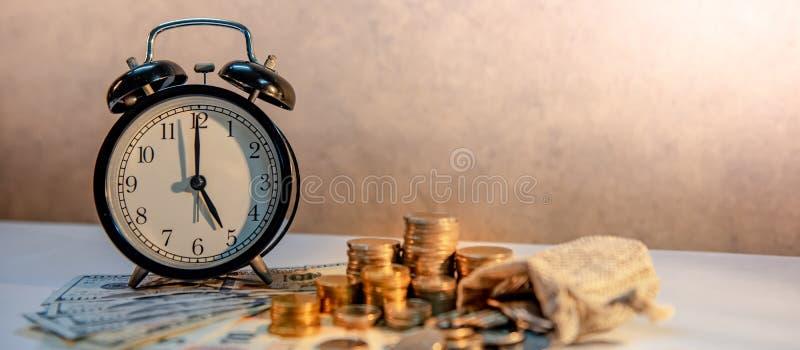 Pila del reloj y de la moneda en la tabla Inversi?n del tiempo fotografía de archivo libre de regalías