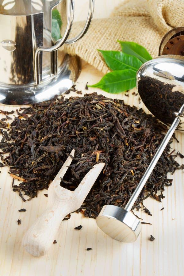Pila del té negro, tetera, cucharada de madera imágenes de archivo libres de regalías