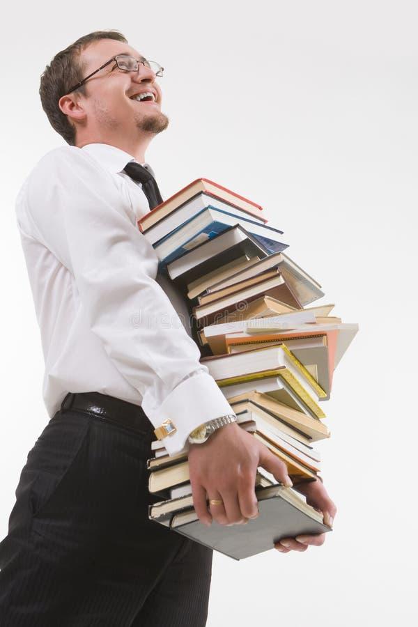 Pila della holding del giovane di libri immagine stock