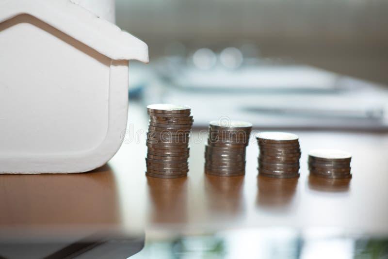 pila della moneta & modello della casa piano per l'acquisto della proprietà ipoteca l immagini stock libere da diritti