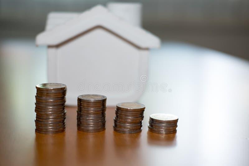 pila della moneta & modello della casa piano per l'acquisto della proprietà ipoteca l fotografia stock libera da diritti