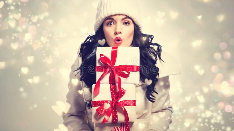 Pila della tenuta della giovane donna di contenitori di regalo fotografie stock libere da diritti