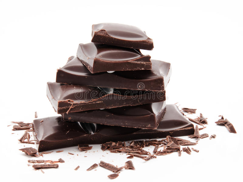 Pila delle barre di cioccolato fondente con le briciole isolate su un bianco immagine stock