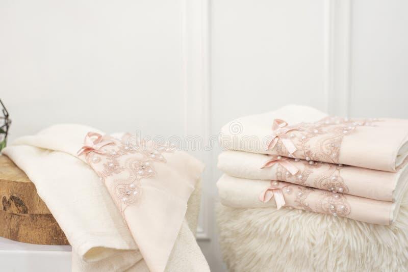 Pila di asciugamani bianchi e rosa molli puliti con pizzo e le perle Fiori su fondo immagine stock libera da diritti