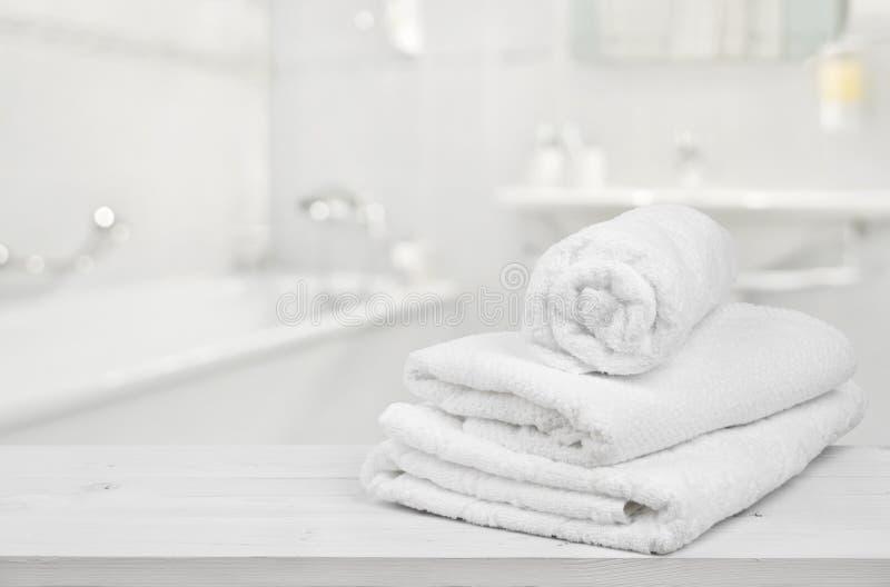 Pila di asciugamani bianchi piegati della stazione termale sopra il fondo vago del bagno immagine stock libera da diritti