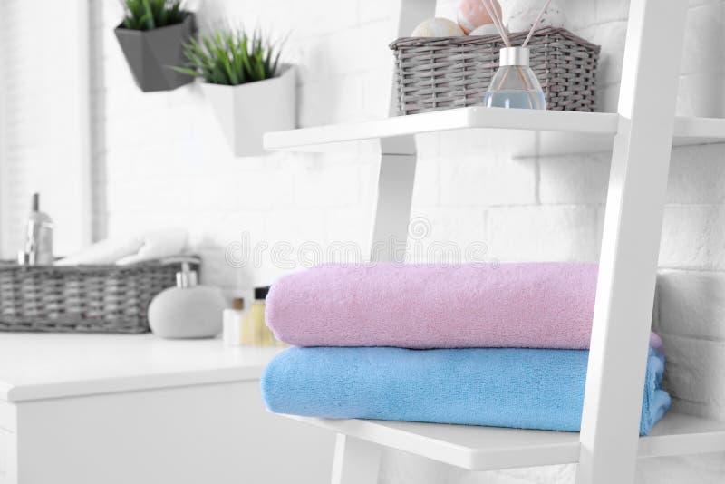 Pila di asciugamani freschi sullo scaffale in bagno immagine stock libera da diritti