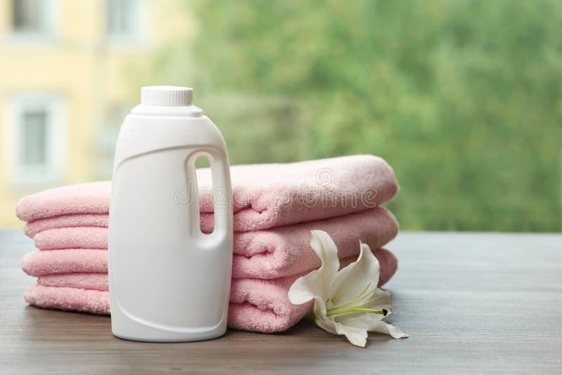 Pila di asciugamani puliti con il giglio ed il detersivo sulla tavola contro fondo vago immagine stock