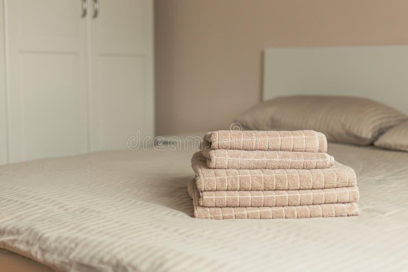 Pila di asciugamano beige dell'hotel sul letto nell'interno della camera da letto Tonalità d'annata fotografie stock libere da diritti