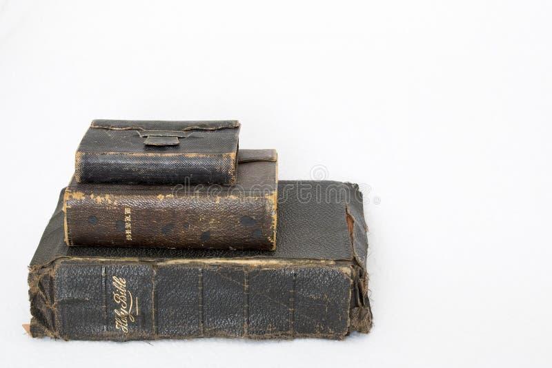 Pila di bibbie antiche su fondo bianco fotografia stock