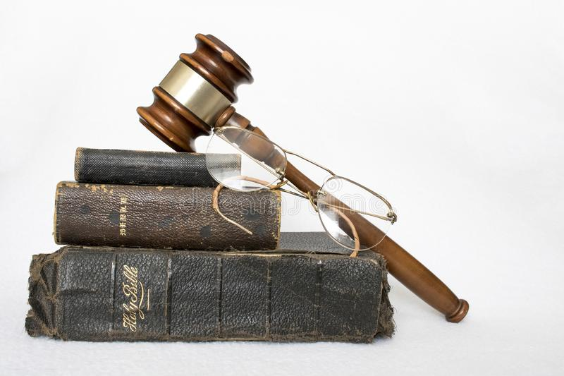 Pila di bibbie di cuoio indossate antiche con Gavel e di vetri su W immagine stock libera da diritti