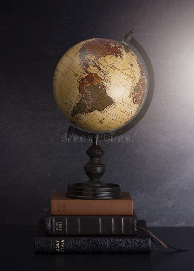 Pila di bibbie e di globo su un fondo scuro immagini stock libere da diritti