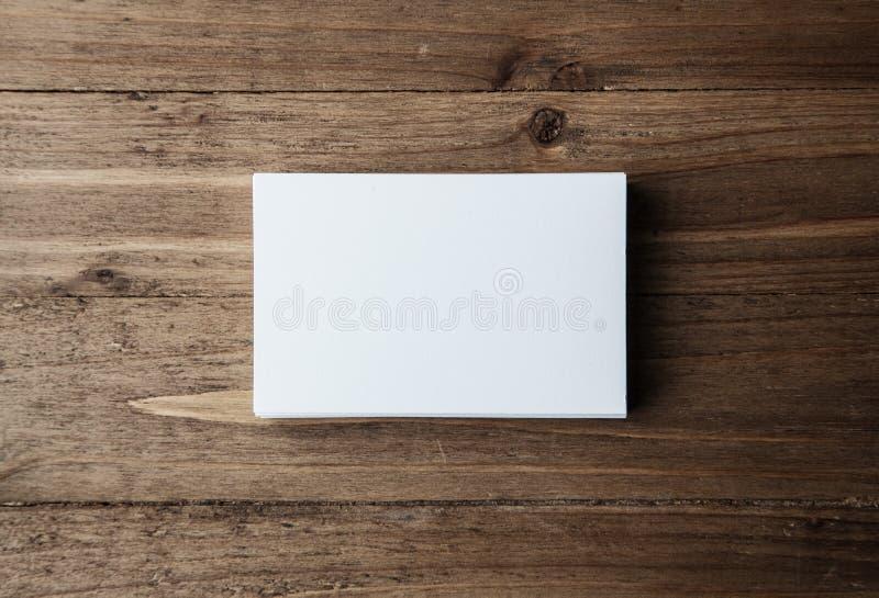 Pila di biglietti da visita bianchi in bianco sull'orizzontale di legno del fondo immagine stock