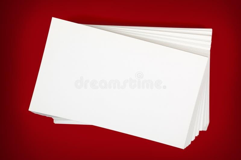 Pila di biglietti da visita sopra fondo rosso fotografia stock libera da diritti
