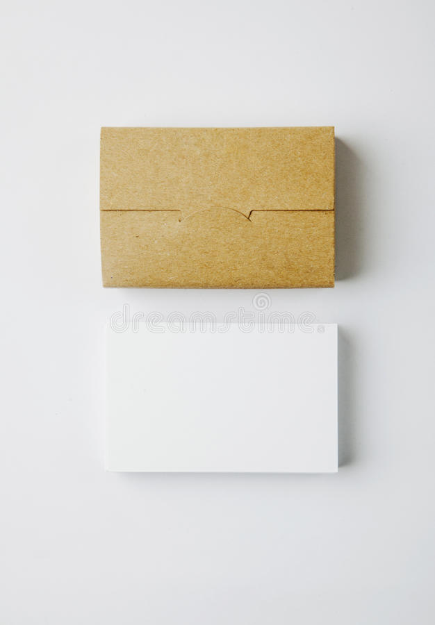 Pila di biglietti da visita e di scatola di carte bianchi in bianco del mestiere su fondo bianco verticale fotografie stock