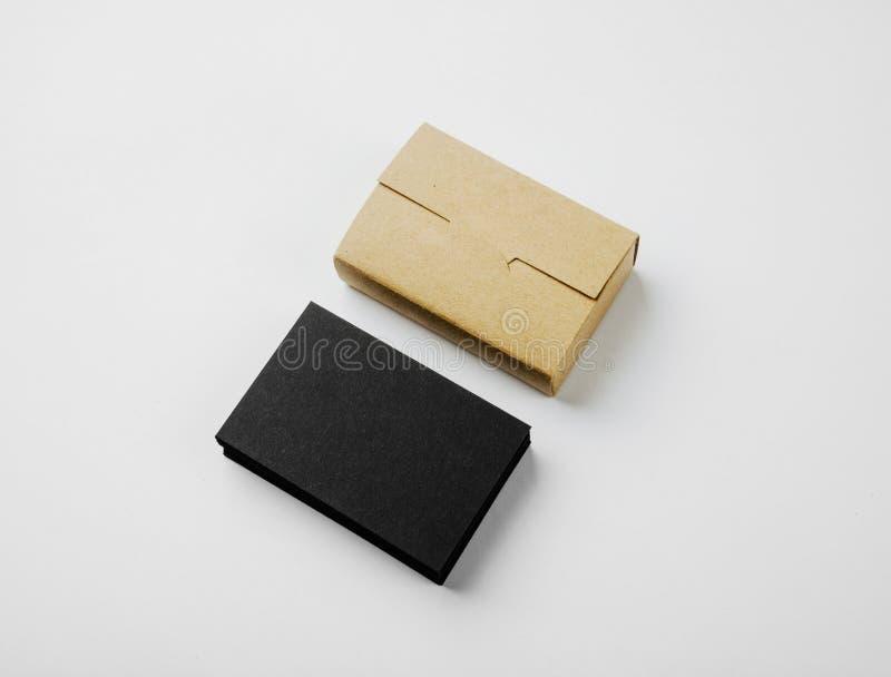 Pila di biglietti da visita e di scatola di carte neri in bianco del mestiere su fondo bianco fotografie stock libere da diritti