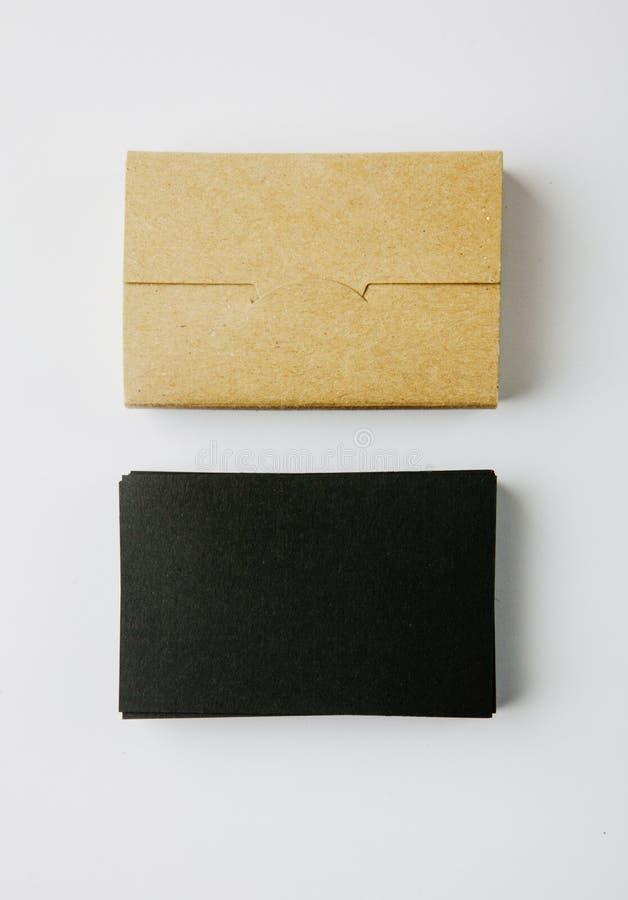 Pila di biglietti da visita e di scatola di carte neri in bianco del mestiere su fondo bianco verticale immagini stock libere da diritti