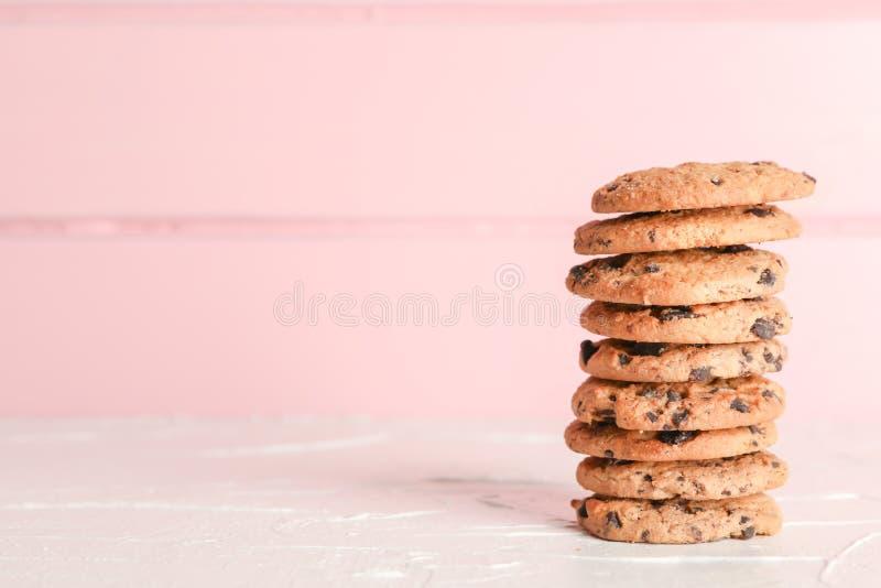 Pila di biscotti di pepita di cioccolato saporiti su fondo di legno fotografie stock