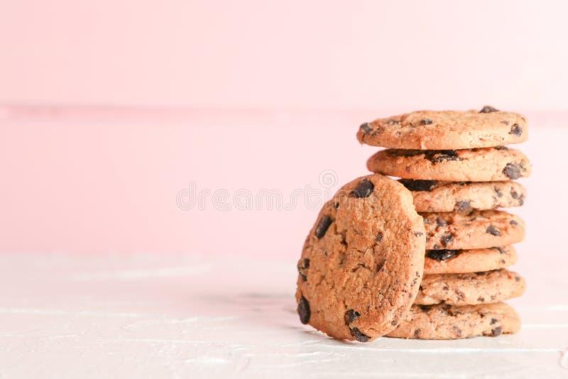 Pila di biscotti di pepita di cioccolato saporiti su fondo di legno fotografia stock libera da diritti