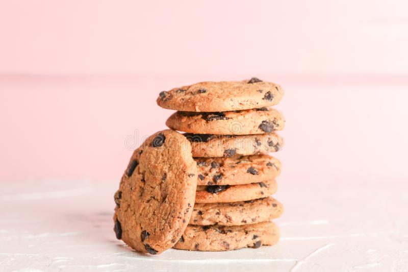 Pila di biscotti di pepita di cioccolato saporiti su fondo di legno fotografia stock
