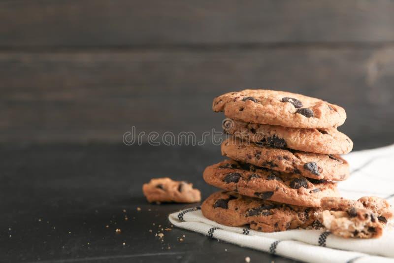 Pila di biscotti di pepita di cioccolato saporiti sul tovagliolo e sul fondo di legno fotografia stock