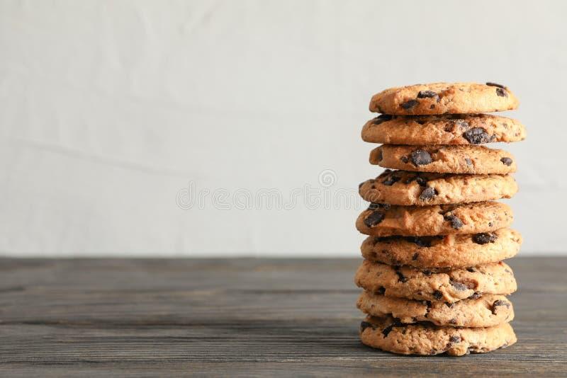 Pila di biscotti di pepita di cioccolato saporiti sulla tavola di legno immagine stock libera da diritti