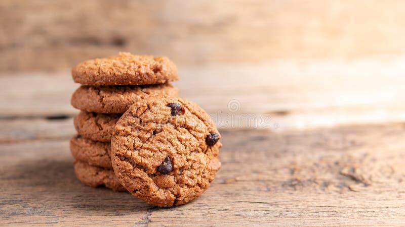 Pila di biscotti di pepita di cioccolato sulla tavola di legno fotografia stock libera da diritti