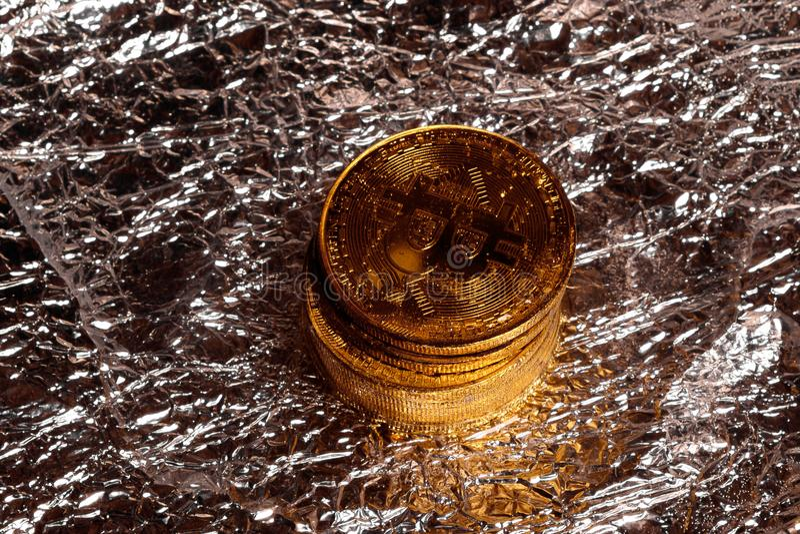 Pila di bitcoins fisici dorati su un fondo della stagnola fotografie stock