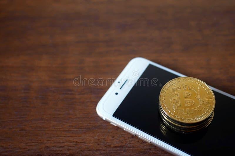 Pila di Bitcoins fisico con valuta virtuale dello smartphone concentrata immagine stock