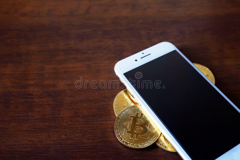 Pila di Bitcoins fisico con valuta virtuale dello smartphone concentrata immagini stock libere da diritti