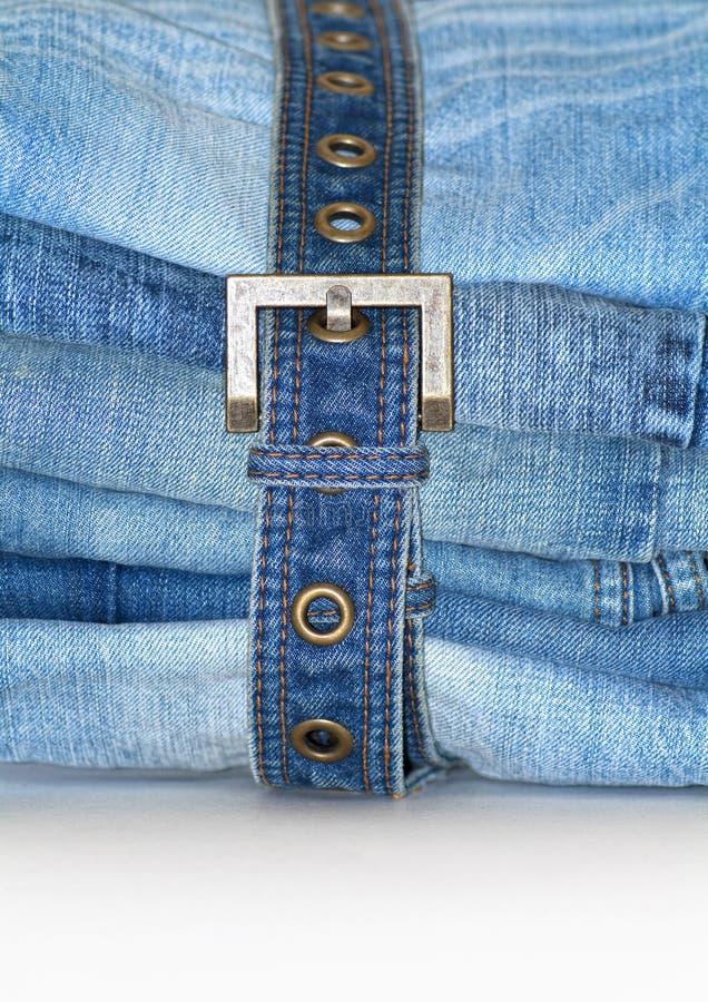 Pila di blue jeans piegate con la fascia del tralicco fotografia stock libera da diritti