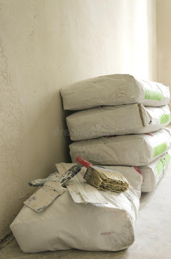 Pila di borse del cemento sul pavimento contro gli strumenti del costruttore e della parete Processo della riparazione Colpo vert immagine stock libera da diritti