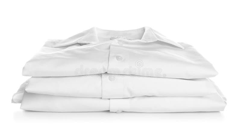 Pila di camice piegate pulite su fondo bianco fotografia stock