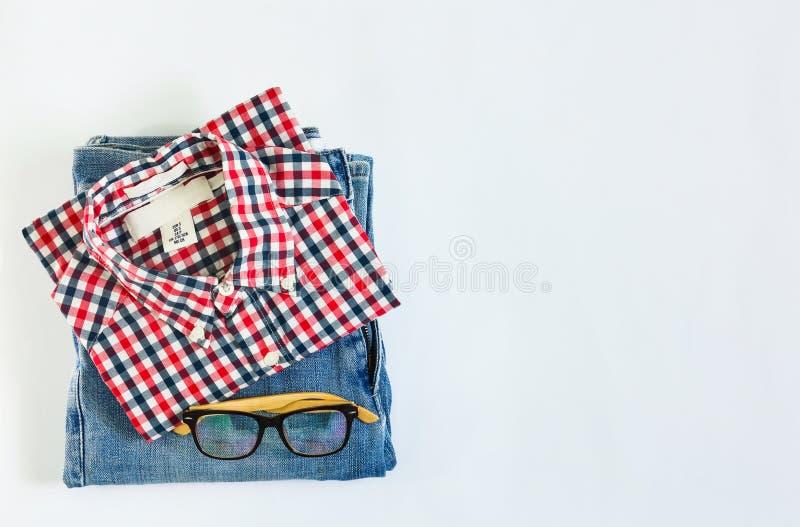 Pila di camicia di plaid e di tralicco blu con i vetri su fondo bianco immagini stock