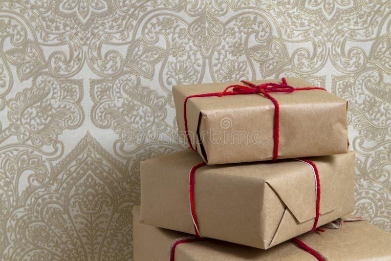 Pila di contenitori di regalo sul fondo della carta da parati immagini stock