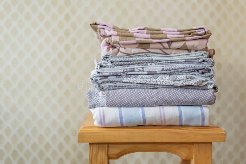 Pila di coperte di strati del tessuto su uno scaffale di legno f immagine stock