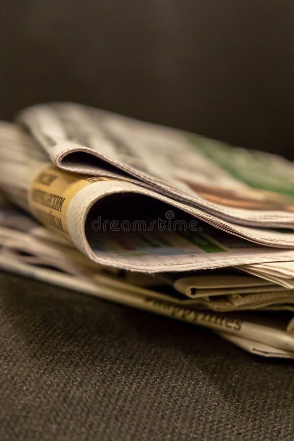 Pila di corrispondenza di carta di mattina dei periodici dei giornali un bordo del primo piano del plesso e di fonte di notizie immagine stock libera da diritti
