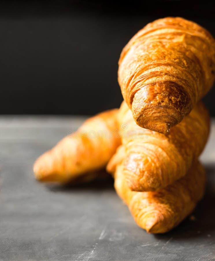 Pila di croissant butirrosi di recente al forno su fondo nero Manifesto golden delicious appetitoso della crosta per la pasticcer immagini stock libere da diritti